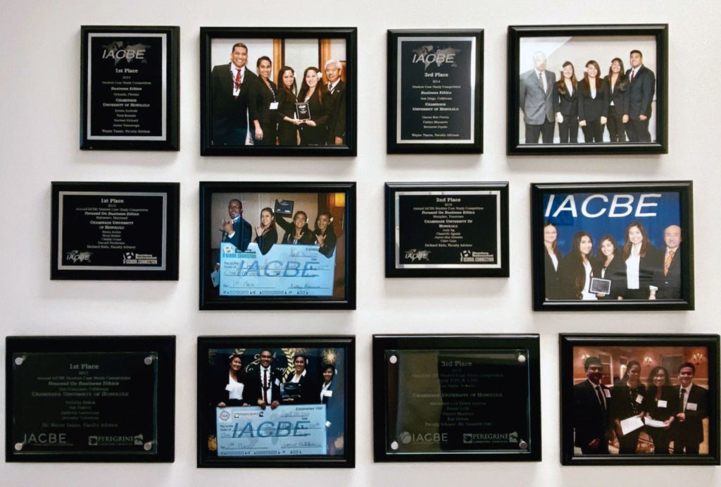 """The """"Wall of Fame."""" A display of pictures of previous student teams and IACBE Awards received inside the School of Business and Communication at Chaminade University of Honolulu."""